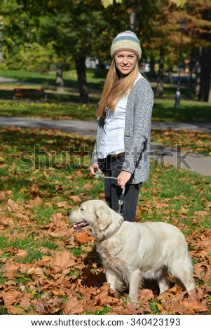 Young, cute girl wearing cardigan and woolen cap, standing in autumn leaves in a park together with her pet, golden retriever dog - stock photo