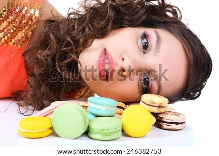 Young cute girl with tasty macaroon on white background - stock photo