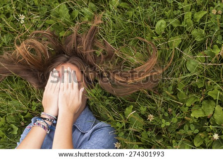 Young cute girl with tousled long hair lying on the green grass covering his face with his hands. - stock photo