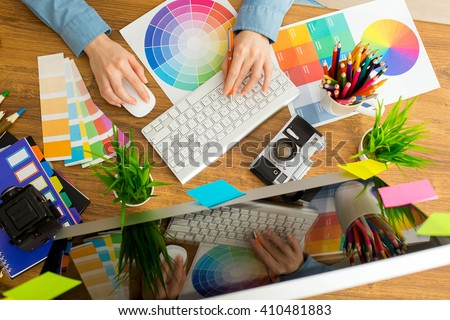 Young cute Graphic designer using graphics tablet to do his work at desk - stock photo