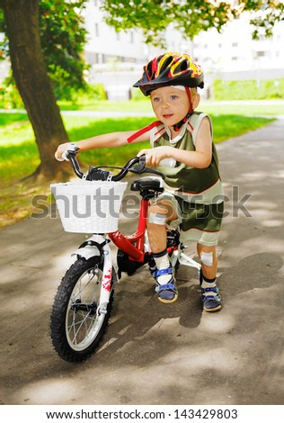 Young cute kid learning to ride a bike - stock photo