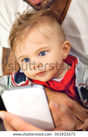 Young cute little boy is watching onto a sellphone with affection embraced by his father. - stock photo