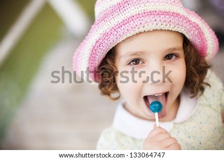 Young cute little girl tasting a lollypop - stock photo