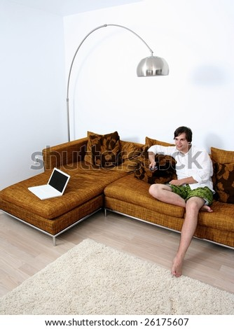 Young cute male relaxing on couch watching TV - stock photo
