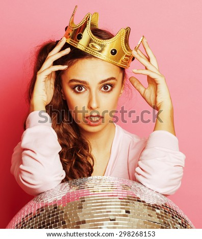 young cute party girl on pink background with disco ball and crown smiling - stock photo