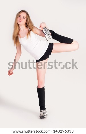 Young cute woman in sportswear show athletic skill at white background - stock photo