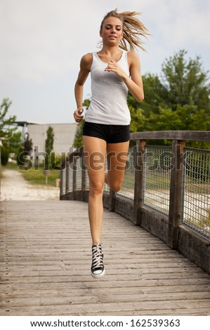 Young cute woman jogging in city park - stock photo