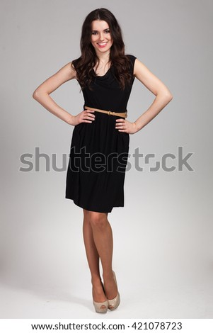 Young cute woman posing in black dress - stock photo
