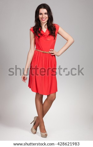 Young cute woman posing in red dress - stock photo