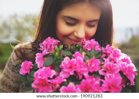 Young cute woman smelling pink flowers - stock photo