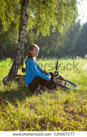 Young cyclist enjoying relaxation in spring in the morning park sitting in the birch trunk - stock photo