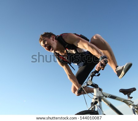 Young cyclist screaming during fall - stock photo