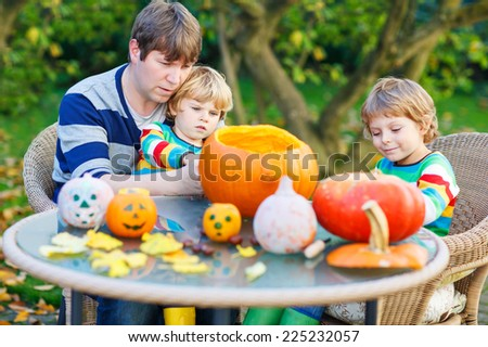 Young dad and his two little sons making jack-o-lantern for halloween in autumn garden, outdoors. Family having fun together - stock photo