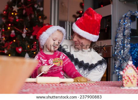 Young dad and little daughter in Santa hat bake Christmas gingerbread cookies - stock photo