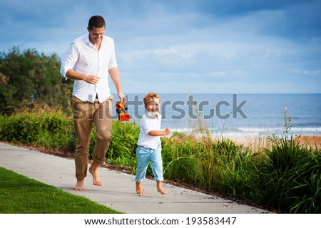 Young dad and son having fun running at the beach footpath in summer - stock photo