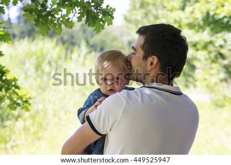 Young dad with a child in the park - stock photo