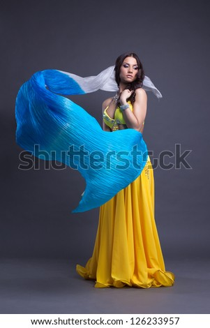 Young dancer in yellow costume dance with fantail - stock photo