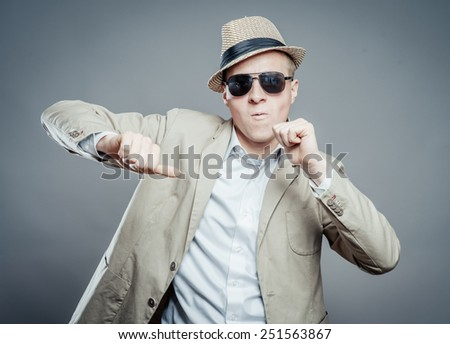 Young dancing  businessman in elegant  suit, hat and sun glasses. - stock photo