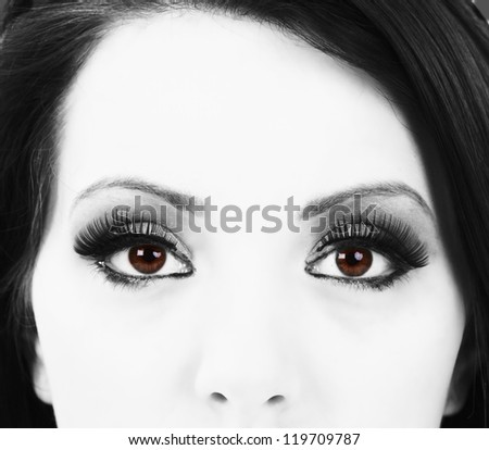 Young dark haired woman with hazel eyes, monochrome upper face - stock photo