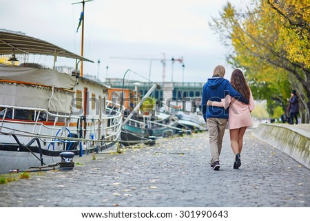 Young dating couple in Paris on a bright fall day, walking together by the Seine, colorful autumn leaves in the background - stock photo