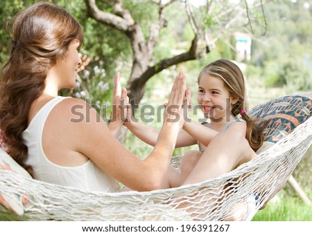 Young daughter and mother sitting together on a hammock in a holiday home garden playing games and clapping their hands, having fun during a sunny summer day on vacation. Active family lifestyle. - stock photo