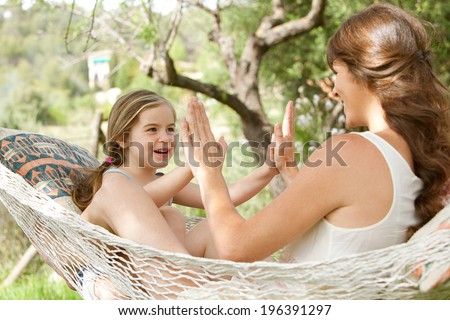 Young daughter and mother sitting together on a hammock in a holiday home garden playing games and clapping their hands, having fun during a sunny summer vacation. Active family lifestyle. - stock photo