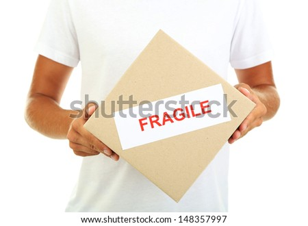 Young delivery man holding parcels, isolated on white - stock photo