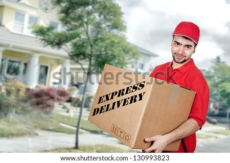 Young delivery man in red uniform holding the box - stock photo