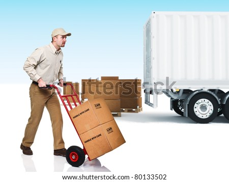 young delivery man with red handtruck - stock photo