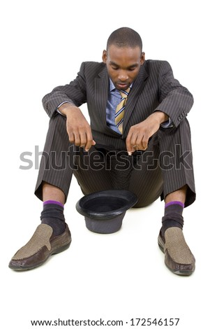 young depressed black businessman sitting in a corner - stock photo
