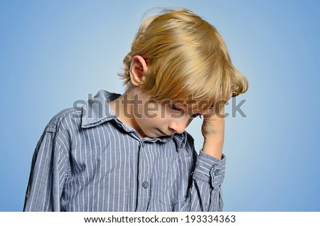 Young depressed boy on blue background - stock photo
