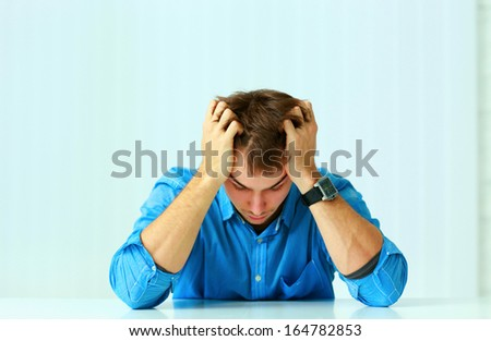 Young depressed businessman sitting at the table and looking down in office - stock photo