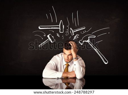 Young depressed businessman sitting under white drawn beating hammer marks - stock photo