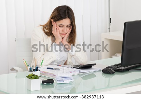 Young Depressed Businesswoman Calculating Invoice In Office - stock photo