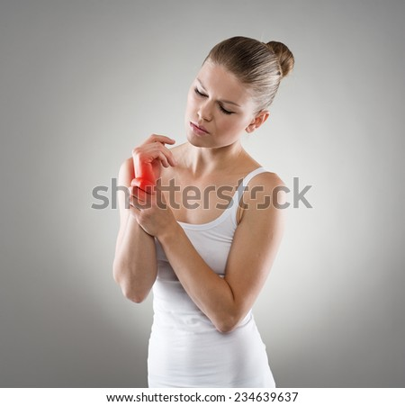 Young depressed female touching her injured wrist in pain. Hand sprain and therapy. Medicine and health concept.  - stock photo