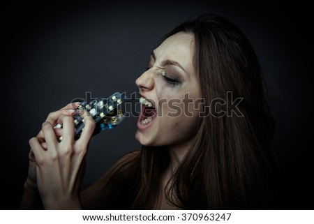 Young depressed woman ussing pills or drugs - stock photo