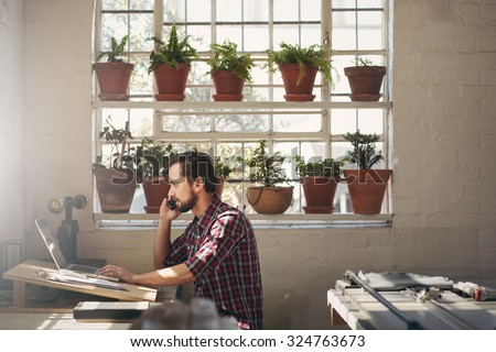 Young designer entrepreneur looking at his laptop while talking on his phone in his studio work space - stock photo