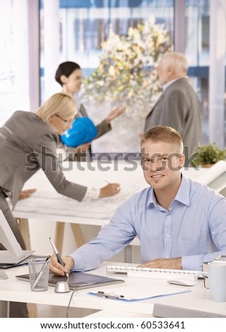 Young designer sitting at desk, colleagues working in background of bright office.? - stock photo