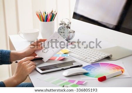 Young designer woman with beautiful hands with idea sign and tablet - stock photo