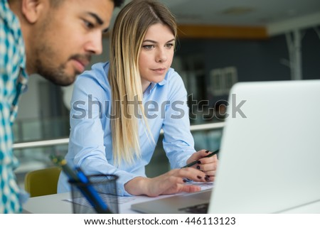 Young designers using laptop in office. Feeling exhausted. - stock photo