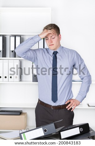 Young despaired businessman is standing in front of many files on his desk in the office. He holds one hand at his head. A shelf is in the background. The man is looking to the files. - stock photo