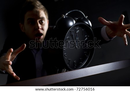 Young desperate business person in dark suit at office desk reaching alarm clock showing five minutes to twelve o'clock and trying to rescue his business, low-key image isolated on black background. - stock photo