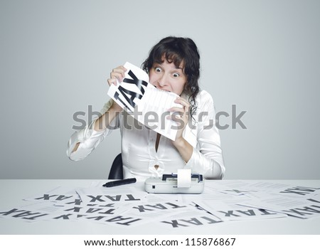 Young desperate woman at her paperwork covered desk biting a tax form - stock photo