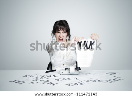 Young desperate woman at her paperwork-covered desk ripping up a tax form staring at the camera - stock photo