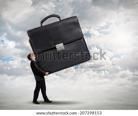 Young determined businessman carrying big heavy suitcase - stock photo