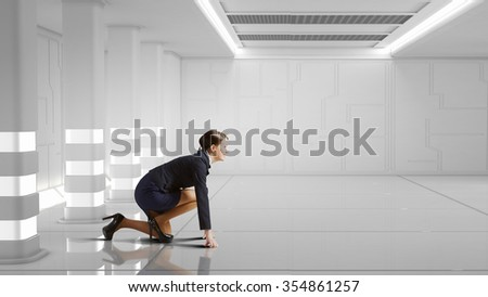Young determined businesswoman standing in start position ready to compete - stock photo