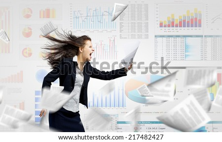 Young determined businesswoman walking against strong wind - stock photo