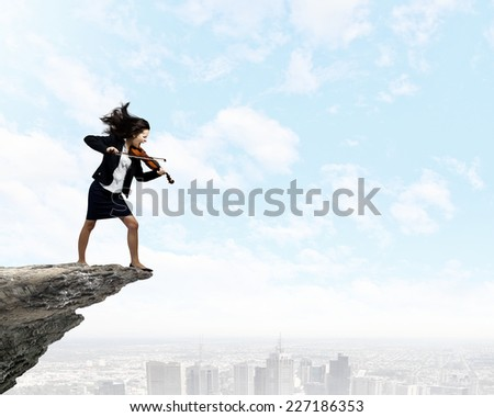 Young determined woman in black suit playing violin - stock photo