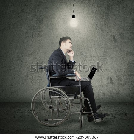 Young disabled entrepreneur with laptop sitting on wheelchair while looking up at lightbulb - stock photo
