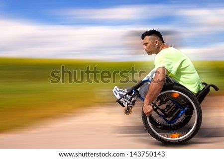 young disabled man doing exercises with his wheelchair outside in summer - stock photo